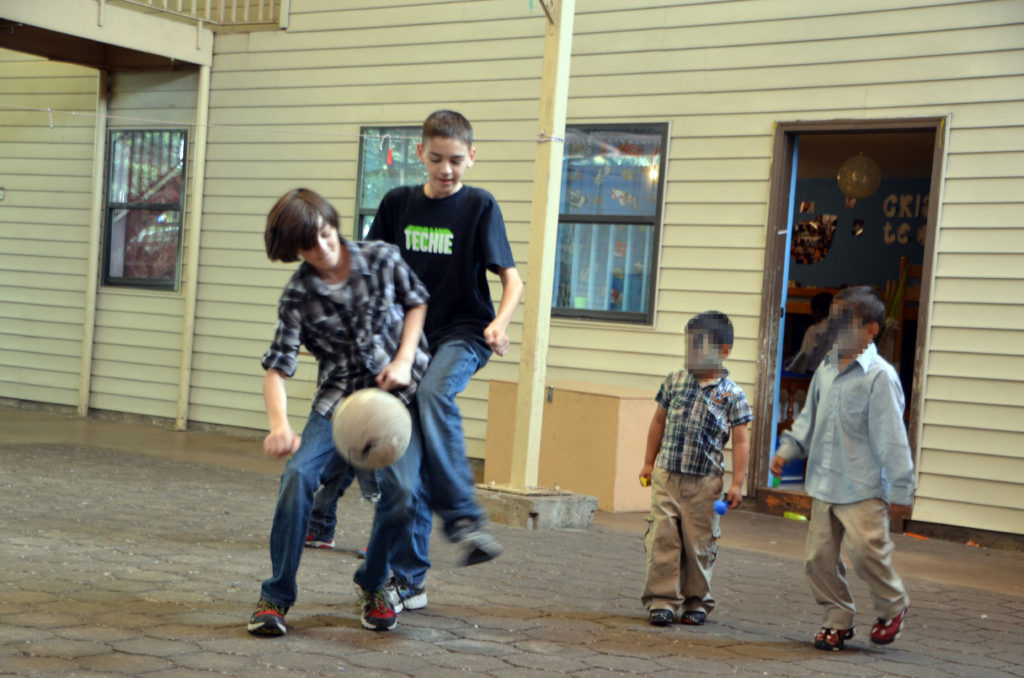 boys playing soccer at children's home blurred